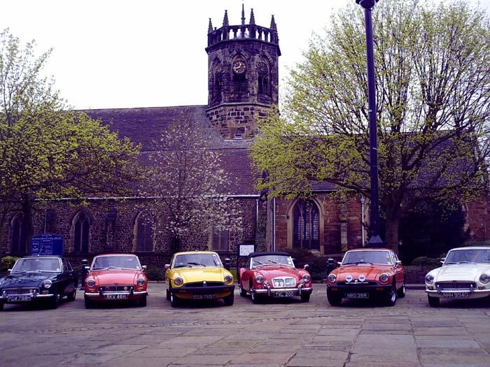 A group of MG enthusiasts assemble on St Georges day in Atherstone market square for a photo shoot.Unfortunately two chavs turned up in rubber bumper cars to interupt the furious pollishing of the chrome bumper brigade!